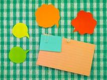 五颜六色的气球和笔记(绿色织品背景) 免版税库存图片
