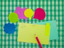 五颜六色的气球和笔记(绿色织品背景) 库存图片