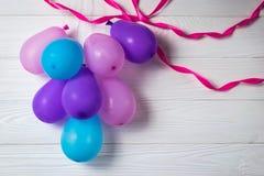 五颜六色的气球堆在白色背景的与丝带集会生日贺卡 免版税库存照片