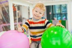 五颜六色的气球围拢的小男孩 免版税库存图片
