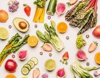 五颜六色的水果和蔬菜舱内甲板放置与一半的背景桔子、鲕梨、柑橘、苹果和莓果,顶视图 免版税库存照片