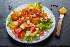 五颜六色的沙拉、新鲜的绿色叶子和切的红色和黄色西红柿,白色板材,刀子,黑石背景 免版税图库摄影