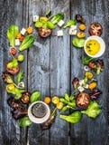 五颜六色的沙拉成份用蕃茄和希腊白软干酪在土气蓝色木背景,圆的框架 免版税图库摄影