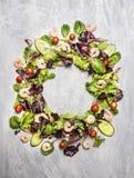 五颜六色的沙拉成份用蕃茄和虾,圆的框架,在浅灰色的木背景 库存图片