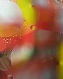 五颜六色的油在水-抽象背景中滴下 免版税库存照片
