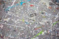 五颜六色的油漆在肮脏的老灰色墙壁背景纹理飞溅 免版税库存图片