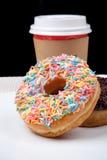 五颜六色的油炸圈饼和咖啡在白色板材有黑背景 免版税库存照片