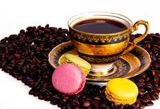 五颜六色的法国蛋白杏仁饼干和咖啡豆在cupof cofee旁边 库存图片