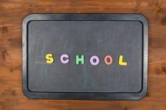 五颜六色的泡沫信件的学校词在黑板的 库存照片