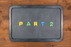 五颜六色的泡沫信件的第2部分标题在黑板的 免版税库存照片