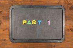 五颜六色的泡沫信件的第1部分标题在黑板的 免版税库存图片