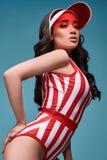 五颜六色的泳装的美丽的迷人的亚裔女孩在明亮的背景 免版税库存图片