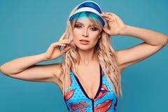五颜六色的泳装的美丽的迷人的白肤金发的女孩 免版税库存图片