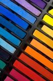 五颜六色的淡色蜡笔和书的垂直的图象 库存图片