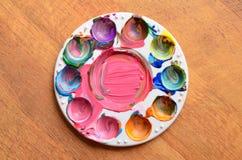 五颜六色的混杂的油漆残余在调色板的 库存图片