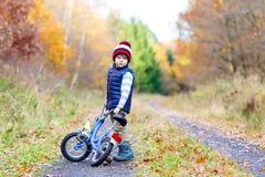 五颜六色的温暖的衣裳的小孩男孩在秋天驾驶自行车的森林公园 循环在晴朗的秋天天的活跃孩子  免版税库存图片