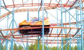 五颜六色的游乐园乘驾汽车快速地与全速匹配 库存照片