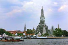 五颜六色的游船和黎明寺寺庙在曼谷,泰国 免版税库存照片