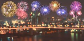 五颜六色的烟花在被弄脏的bokeh城市夜点燃背景 库存图片