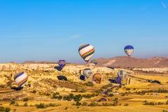 五颜六色的热空气迅速增加飞行在岩石风景和登陆 免版税图库摄影