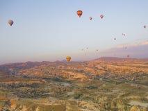 五颜六色的热空气迅速增加飞行在谷在卡帕多细亚,安纳托利亚,土耳其 火山的山在Goreme国家公园 库存照片