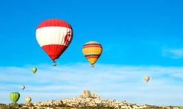 五颜六色的热空气迅速增加飞行靠近Uchisar城堡在日出 免版税图库摄影