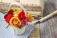 五颜六色的玫瑰和葡萄酒信件篮子  库存图片