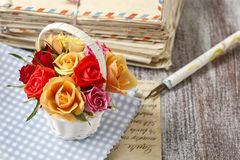 五颜六色的玫瑰和葡萄酒信件篮子  免版税库存照片