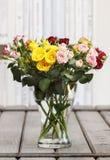 五颜六色的玫瑰花束在玻璃花瓶的在葡萄酒木桌上 免版税库存图片