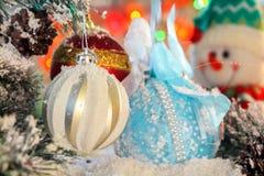 五颜六色的球在圣诞树的积雪的分支垂悬反对快活的雪人和五颜六色的光 免版税库存图片