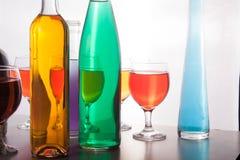 五颜六色的瓶和玻璃在白色背景 图库摄影
