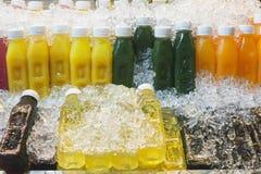 五颜六色的瓶用在冰的新鲜的水果和蔬菜汁在泰国市场上 Lealthy生活方式,旅行概念 免版税库存照片