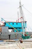五颜六色的生锈的船在有渔夫的雅加达港口在船上 免版税库存图片