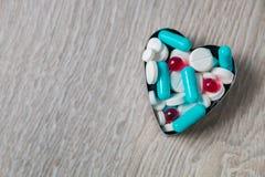 从五颜六色的疗程的上面心脏和药片在灰色木背景 复制空间 顶视图,框架 止痛药,片剂,基因 免版税库存照片