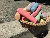 五颜六色的白垩在篮子黏附对凹道艺术在水泥地板 室外家庭活动、孩子学会技能的和天分 免版税图库摄影