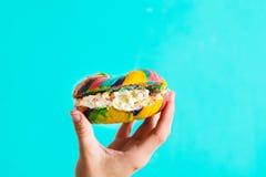 五颜六色的百吉卷用乳酪和在蓝色背景在手中洒 图库摄影