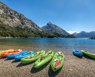 五颜六色的皮船在山包围的湖在巴伊亚卢佩茨在Circuito奇哥-巴里洛切,巴塔哥尼亚,阿根廷 免版税图库摄影