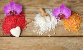 五颜六色的盐幻灯片卫生间的在与兰花花和一块白色心形的石头的一张木桌上 免版税库存照片