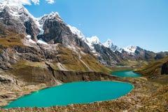 五颜六色的盐水湖和史诗峰顶在山脉Huayhuash,秘鲁 免版税库存照片