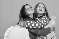 五颜六色的短上衣被加点的睡衣的女孩拿着明亮的枕头 有惊奇的面孔和宽松头发拥抱的孩子 免版税库存图片