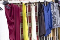 五颜六色的礼服在准备在街道附近被卖的金属棒垂悬了 图库摄影