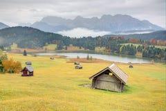 五颜六色的秋天季节的湖Geroldsee,在加米施・帕藤吉兴之间的一个美丽的高山湖和米滕瓦尔德和有雾的Karwend 库存照片