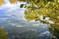 五颜六色的秋天风景在与树的一个晴天与水和云彩 免版税库存照片