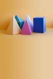 五颜六色的立体图形静物画背景 三维棱镜金字塔长方形立方体在桔子反对 黄色 库存照片