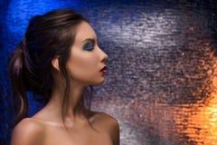 五颜六色的箔背景的美丽的女孩在晚上lig 免版税库存照片