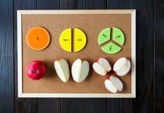 五颜六色的算术分数和苹果作为一个样品在棕色木背景或桌 孩子的有趣的算术 教育 免版税库存图片