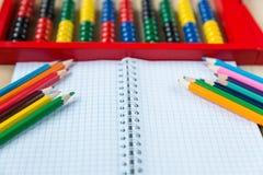 五颜六色的算盘,铅笔,时钟,在木背景的黑板 教育,回到学校 库存照片