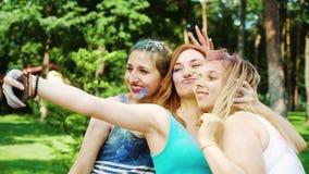 五颜六色的粉末的三个女孩在庆祝侯丽节节日以后做滑稽的selfie 影视素材