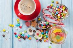 五颜六色的糖果和咖啡在木桌上 库存图片