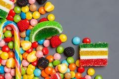 五颜六色的糖果和棒棒糖在石背景 与拷贝空间的顶视图 免版税库存照片